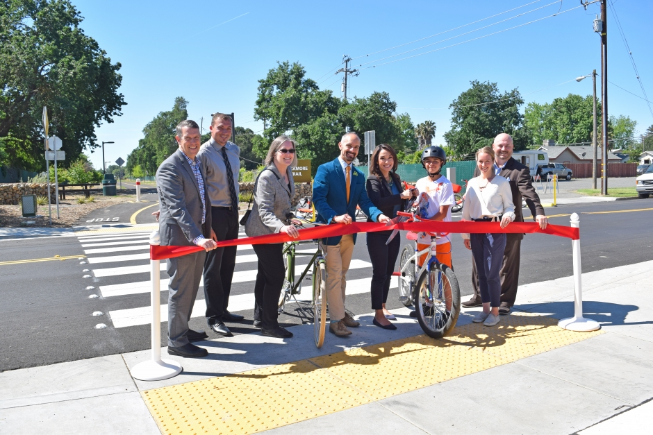 West Sacramento Mayor Christopher Cabaldon, center, and SACOG executive director James Corless, left, help to cut the ribbon on the Sycamore Trail extension on the first day of May is Mike Month.