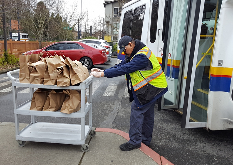 A transit worker loads meals onto a bus.